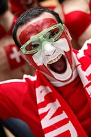 Football fan with their face painted in the Swiss national colours