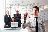 Businessman writing some formulas with group of business people on the background