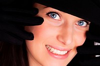 Portrait of a beautiful brunette young woman with gloves and black hat