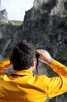 Man wearing an orange windbreaker using binoculars in the mountains.