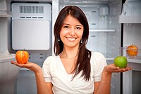 Beautiful woman taking fruits from the fridge and smiling