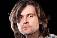 Portrait of handsome man with long hair on black background in the studio