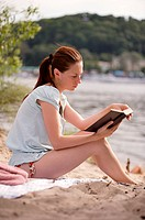 Young girl reading the book on the riverside