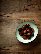 Bowl of chestnuts on wood background