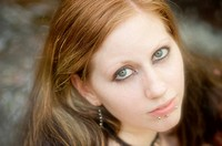 Portrait of a 25 year old redhead woman with dramatic make up and facial pierciengs outdoors