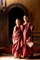 Two novice monks smiling in Shwe Yaunghwe Kyaung monastery  Nyaung Shwe, Myanmar