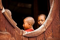 Young monks by the window on Shwe Yaunghwe Kyaung monastery  Nyaung Shwe, Myanmar