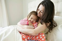 Mom cuddling child in bedroom