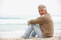 Senior Man On Holiday Sitting On Winter Beach