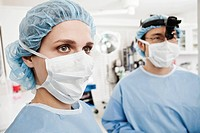 Two surgeons wearing masks in operating theater