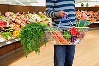 Man holding shopping basket with fresh vegetables in supermarket
