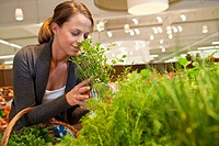 Woman choosing herbs in supermarket