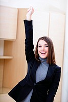 Portrait of happy young woman showing a happy gesture in office