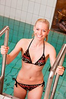 Portrait of a web blond woman on a swimming pool ladder