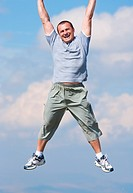 Happy young man hanging from the upper edge of the photo, in the sky. Conceptual shot