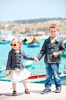 Two little kids near harbor in little charming village of Marsaxlokk in Malta