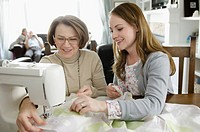 Daughter sewing with senior mother.