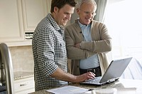 Son helping senior father with surfing the net