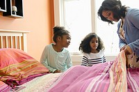 Mom teaching daughters to make a bed