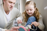 Dad helping young daughter tie shoe laces
