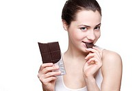 Beautiful young woman eating dark chocolate