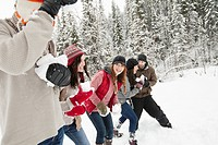 Adults having a snowball fight in the countryside