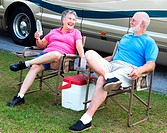 Senior campers sitting in folding chairs outside their motor home.