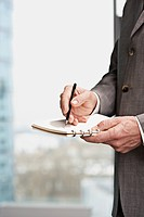 Close up of businessman's hands writing in notepad