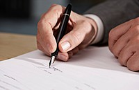 Close up of businessman's hand signing document (thumbnail)