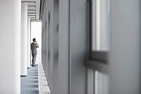 Businessman standing on end of office corridor