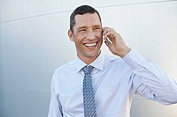Smiling businessman talking via cell phone (thumbnail)