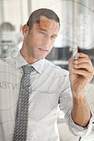 Businessman writing on glass board (thumbnail)
