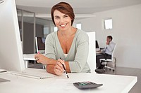 Smiling businesswoman sitting in office (thumbnail)
