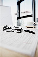 Close up of glasses and pen lying on document