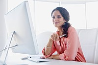 Smiling businesswoman working in office (thumbnail)