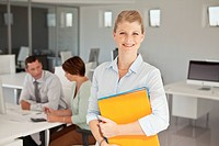 Portrait of smiling business woman holding files (thumbnail)