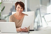 Smiling businesswoman holding document in office (thumbnail)