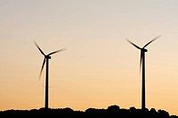 silhouette of two windmills at sunset