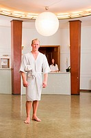 A man wearing a bathrobe in a day spa looking at camera