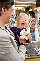 Laughing girl 4_5 with her father in supermarket