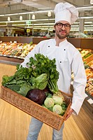 Chef holding basket with vegetables in supermarket