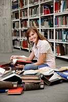 Female student sitting on pile of books