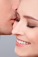 close up portrait of young caucasian couple kissing
