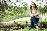 Smiling Teenage Girl Sitting on a Tree trunk alone in the Woods