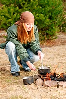 Camping happy woman cook food fire nature