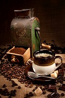Old coffee mill and cup of coffee with chocolate