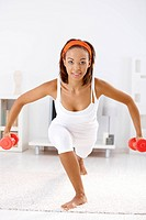 Pretty afro woman exercising with dumbbells, bending on carpet at home.