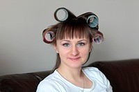 Happy woman poses in rollers at home