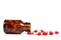 Open happy pill bottle with medicine spilling out of it isolated on white