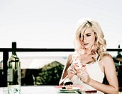 beautiful woman sits at restaurant table with wine by herself
